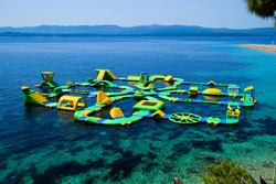 Floating inflatable playground with water slides, swings and trampolines on the island of Brac in Croatia - Aerial view of the serene bay near the Zlatny Rat sand peninsula at Bol