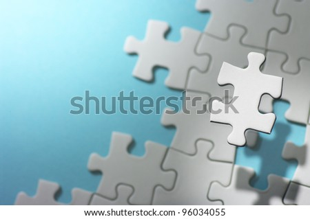 Floating jigsaw puzzle piece in spot light.