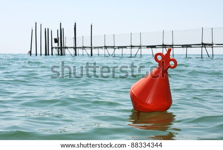 Floating red buoy on the sea