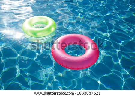 floating rings on blue water swimming pool with waves reflecting in the summer sun