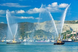 Floating tug boats are spraying jets of water, demonstrating theis firefighting water cannons