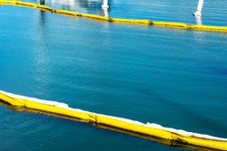 Floating yellow and white oil containment boom on calm water. Pollution concept . A containment boom is a temporary floating barrier used to contain an oil spill.