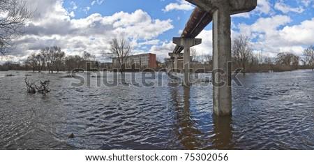 Flood. Little river overflowed its banks. Blue sky