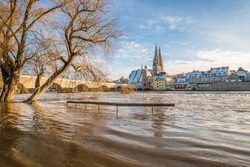 Flood of the river Danube in winter 2021 in Regensburg with view of the cathedral the old town and flooded promenade and the stone bridge, Germany