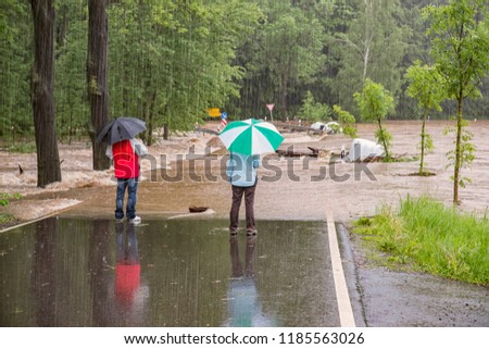 Flood 2013 - 2 passersby stand on the flooded road in rain with umbrellas #1185563026