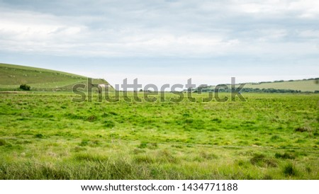 Flood plains, Cuckmere Haven, South Downs, England. A wide view over the flat flood plains of Cuckmere Haven leading into the chalk hills of the South Downs, England. #1434771188