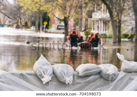 Photo of  Flood Protection Sandbags with flooded homes in the background (Montage)