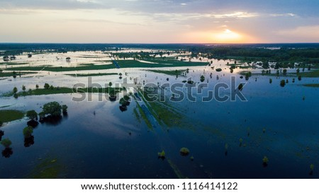 Flooded country road and flooded meadow. Flying above flooded country road in beautiful meadow at sunset. Beautiful meadow landscape in Ukraine. Aerial view.