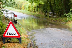 Flooded country road in England, UK with a flood road sign