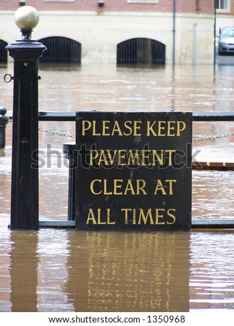 Flooded 'Keep pavement clear sign' on bank of River Ouse, York