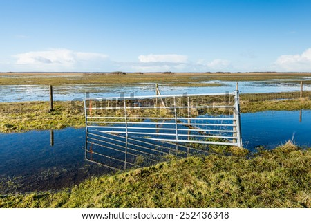 Flooded nature reserve and a crooked steel gate reflected in the mirror smooth water and ice surface on a clear and sunny day in winter.