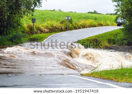 flooded road by an overflowing river, natural disaster Stockfoto ©