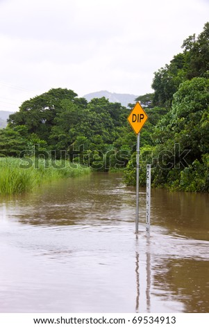 Flooded road with depth indicators and dip sign in Queensland, Australia