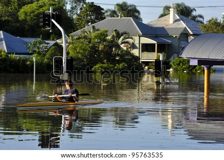 flooded streets: a man uses a canoe to traverse the flooded streets of his suburb. Rosalie, Brisbane, 2011
