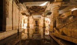 Flooded underground Shiva temple with water reflection in Hampi, Karnataka, India.