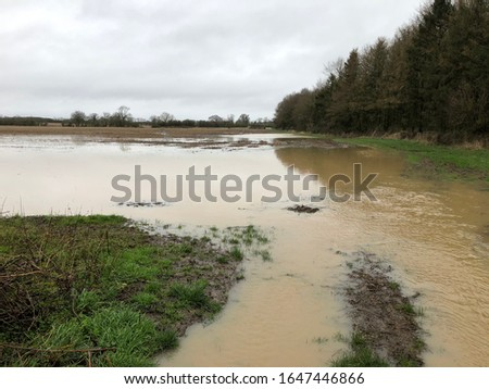 Flooding and storm damage in the UK. Flooded agricultural fields in Oxfordshire countryside. Example of seasonal storms with heavy rainfall and high winds. Agricultural background. stock photo