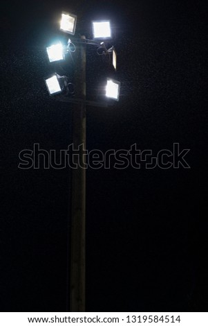Floodlights during light rain in winter. #1319584514