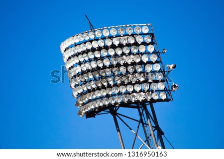 Floodlights mounted on metal post with blue background, Stadium lights #1316950163