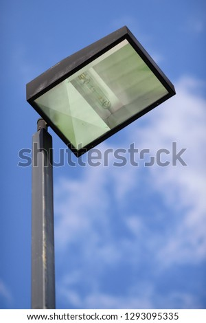 Floodlights mounted on metal post with blue sky background, Lighting pole tower at the sports stadium, car park and ground #1293095335