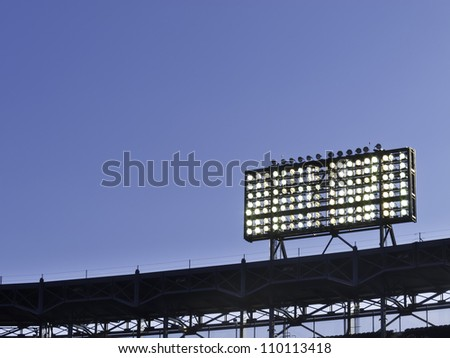 Floodlights over baseball stadium at dusk, with copy space