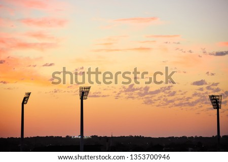 Floodlights silhouetted against an orange, sunset sky. Tranquil landscape, Perth, Western Australia. #1353700946