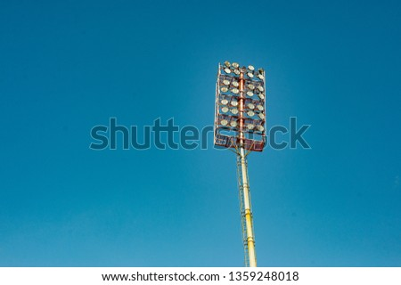 Floodlights with a metal pole for the sports arena. Tall high outdoor stadium spotlights on rigid frame construction with blue sky background #1359248018