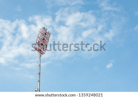 Floodlights with a metal pole for the sports arena. Tall high outdoor stadium spotlights on rigid frame construction with blue sky background #1359248021