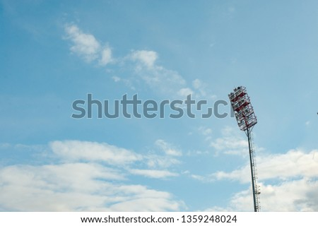 Floodlights with a metal pole for the sports arena. Tall high outdoor stadium spotlights on rigid frame construction with blue sky background #1359248024