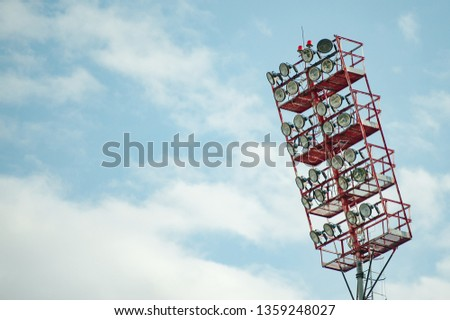 Floodlights with a metal pole for the sports arena. Tall high outdoor stadium spotlights on rigid frame construction with blue sky background #1359248027