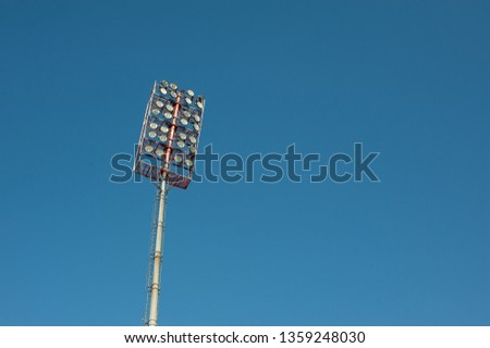 Floodlights with a metal pole for the sports arena. Tall high outdoor stadium spotlights on rigid frame construction with blue sky background #1359248030