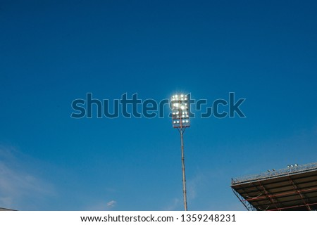 Floodlights with a metal pole for the sports arena. Tall high outdoor stadium spotlights on rigid frame construction with blue sky background #1359248231