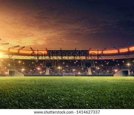 Floodlit soccer field with green grass and dramatic night sky