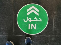 Floor decal/sticker in a shopping mall in Dubai, United Arab Emirates, guides shoppers on social distancing rules to be followed during the Covid-10 pandemic. Arabic text reads 'in'.