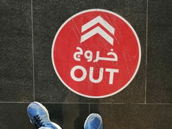 Floor decal/sticker in a shopping mall in Dubai, United Arab Emirates, guides shoppers on social distancing rules to be followed during the Covid-10 pandemic. Arabic text reads 'out'.