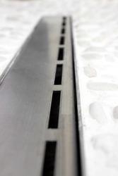 Floor drain in a modern shower, linear floor level shower close up