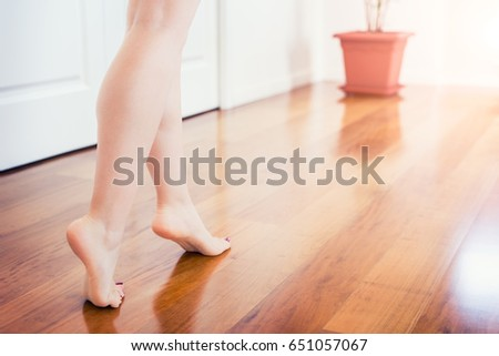 Floor heating. Young woman walking in the house on the warm floor. Gently walked on parquet floor.