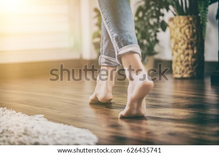 Floor heating. Young woman walking in the house on the warm floor. Gently walked the wooden panels. #626435741