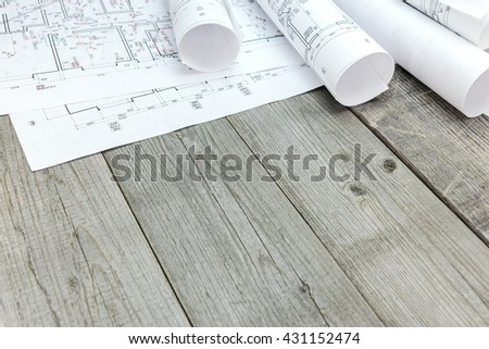 floor plan drawings with architectural blueprint rolls on wooden desk