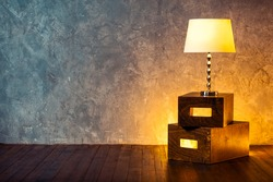 Floor retro lamp on two boxes in the room with a wooden floor and grunge texture wall