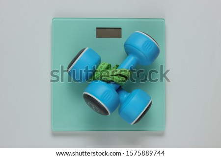 Floor scales and dumbbell wrapped with measuring tape on white background. Sport concept, losing weight, fitness training. Studio shot. Top view
