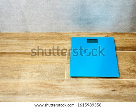 floor scales. Blue scales on a wooden floor in the bathroom. Gray wall Maintaining the right weight, losing weight, fighting obesity.