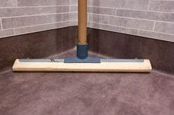 floor scraper stading on dry floor in bathroom