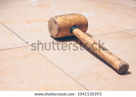 Floor tiles close-up, on the tile plastic white tile crosses and tile mallet, professional tool #1041130393