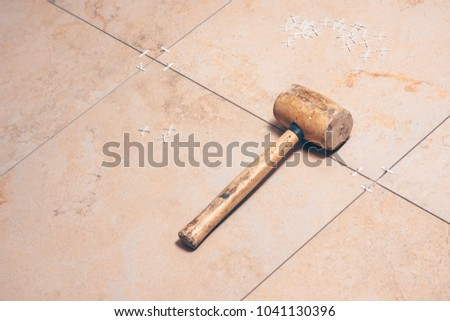Floor tiles close-up, on the tile plastic white tile crosses and tile mallet, professional tool #1041130396
