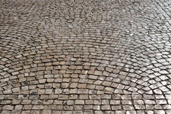Floor tiles on a public street in Lisbon,Portugal.Old stone paved street.Cobblestone road pavement texture.Stone walkway abstract background.