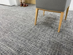 Flooring textile carpet texture. Modern chair textile mix wooden on carpet floor in office room. Harmony and casual interior room design. People standing while waiting service at counter.