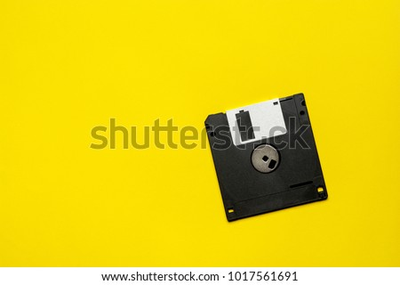 floppy data storage diskette on yellow background with copy space