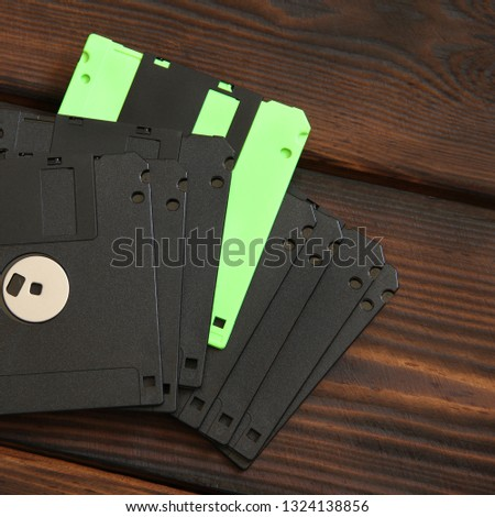 Floppy disks and disks on wooden background