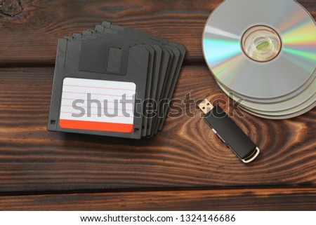 Floppy disks, USB flash drive and disks on a wooden background