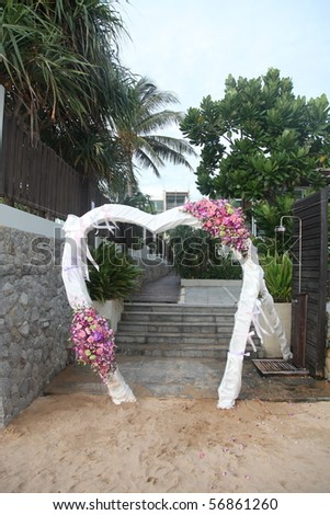 Floral archway at a wedding ceremony on the beach.